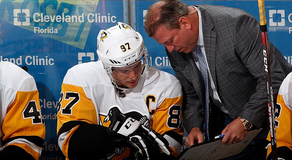 SUNRISE, FL - FEBRUARY 8: A fan has a message for Sidney Crosby #87 of the Pittsburgh Penguins while he chats with Assistant Coach Mark Recchi during a break in the action against the Florida Panthers at the BB&T Center on February 8, 2020 in Sunrise, Florida. (Photo by Eliot J. Schechter/NHLI via Getty Images)