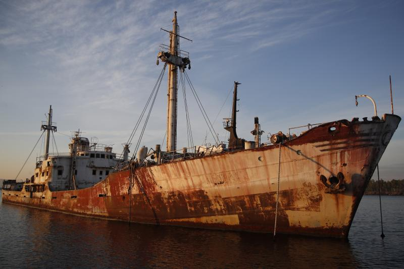 "In this Friday, Dec. 4, 2018 photo, an abandoned ship is tied up in the Gulf of Elefsina, west of Athens. Dozens of abandoned cargo and passenger ships lie semi-submerged or completely sunken around the Gulf of Elefsina, near Greece's major port of Piraeus. Now authorities are beginning to remove the dilapidated ships. Some of them have been there for decades, leaking hazards like oil into the environment and creating a danger to modern shipping. One expert calls the abandoned ships ""an environmental bomb."" (AP Photo/Thanassis Stavrakis)"