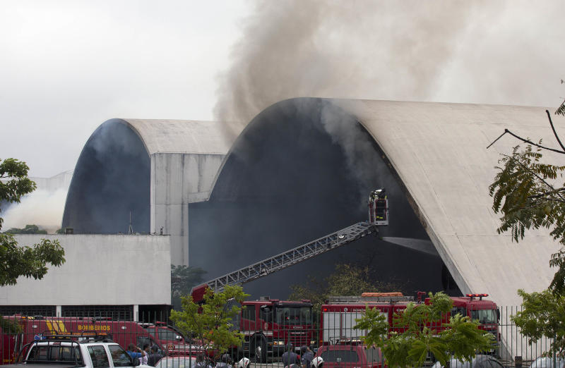 Firefighters watch from a cherry picker as water is sprayed into the Simon Bolivar Auditorium at the Latin America Memorial in Sao Paulo, Brazil, Friday, Nov. 29, 2013. The fire department of Brazil's biggest city says a fire swept through the large auditorium that is part of the political, cultural and leisure complex designed by famed architect Oscar Niemeyer. No casualties were reported. Two firefighters had to be treated for smoke inhalation. (AP Photo/Andre Penner)