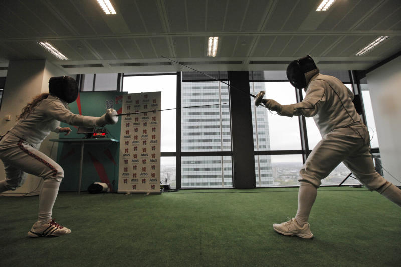 British fencing athletes train during a media event to showcase the technology systems that are used in the sport, at London 2012 Olympic games Technology Operations Centre (TOC) in London's Canary Wharf financial district, Tuesday, July 3, 2012. The technology experts who will run the 11,000 computers and servers at the logistical heart of London's 2012 Olympic Games say they are confident of defending their systems against attempted cyber attacks.Its systems handle venue scoreboards, tournament data, accreditation and workforce management. (AP Photo/Lefteris Pitarakis)
