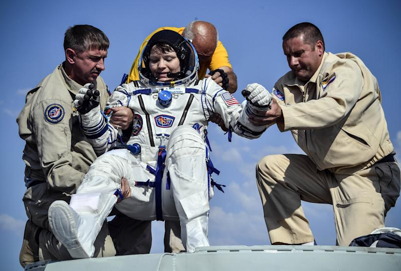 Ground personnel help NASA astronaut Anne McClain to get out of the Soyuz MS-11 capsule shortly after landing in a remote area outside Zhezkazgan, Kazakhstan June 25, 2019. Alexander Nemenov/Pool via REUTERS