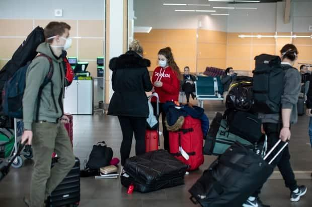 Passengers are shown at the Vancouver International Airport in March 2020. Travellers will not be able to book accommodations outside of their local health authority for the next five weeks until May 24, the end of the long weekend.