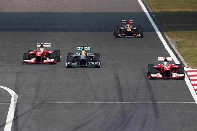 SHANGHAI, CHINA - APRIL 14: Fernando Alonso (R) of Spain and Ferrari and team mate Felipe Massa (L) of Brazil and Ferrari overtake Lewis Hamilton (C) of Great Britain and Mercedes GP on the main straight during the Chinese Formula One Grand Prix at the Shanghai International Circuit on April 14, 2013 in Shanghai, China. (Photo by Clive Mason/Getty Images)
