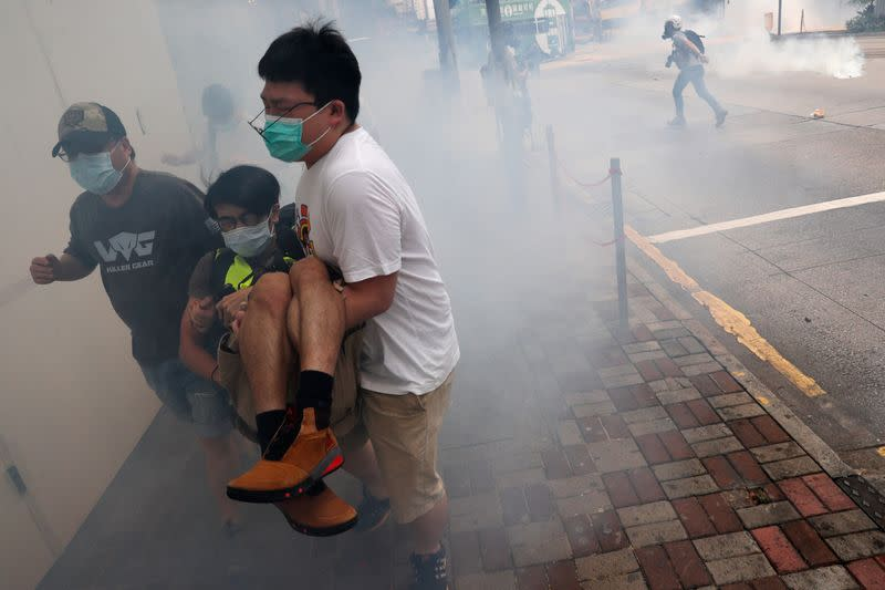 Anti-government protesters run away from tear gas during a march against Beijing's plans to impose national security legislation in Hong Kong