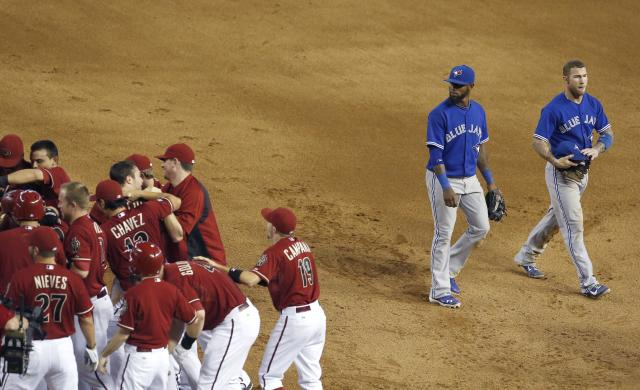 As the Arizona Diamondbacks celebrate a walkoff game-winning hit by Willie Bloomquist, Toronto Blue Jays' Brett Lawrie, right, and teammate Jose Reyes walk past in the 10th inning of a baseball game on Wednesday, Sept. 4, 2013, in Phoenix. The Diamondbacks defeated the Blue Jays 4-3. (AP Photo/Ross D. Franklin)
