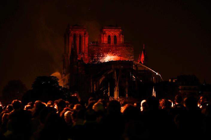 Bystanders look on as flames and smoke billow from the roof at Notre-Dame Cathedral in Paris on April 15, 2019. (Photo: Philippe Lopez/AFP/Getty Images)