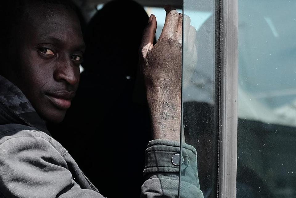 A rescued migrant with a number on his right arm, sits on bus at the Sicilian harbour of Catania, Italy, on April 23, 2015 (AFP Photo/Alberto Pizzoli)