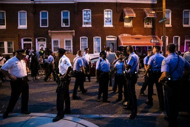 PHOTO: Officers gather for crowd control near a massive police presence set up outside a house as they investigate an active shooting situation, in Philadelphia, Aug. 14, 2019. (Matt Rourke/AP)