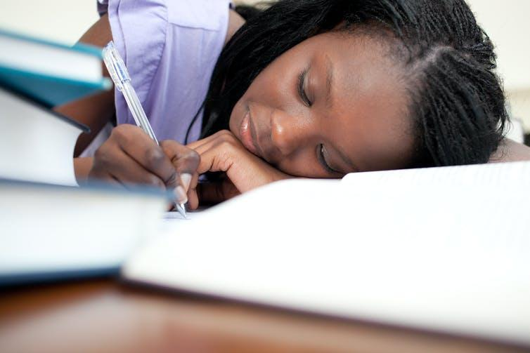 Girl leaning on her arm writing