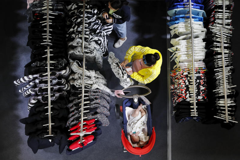 A woman checks on a clothing price tag at a fashion retailer store having promotion sale at a shopping mall in Shenzhen, China's Guangdong province, Friday, Nov. 1, 2019. Chinese leaders are counting on consumers to power the economy, replacing trade and investment as Beijing fights a tariff war with Washington. But shoppers are jittery about possible job losses and are tightening their belts, hurting sales of cars, real estate and other big-ticket items. (AP Photo/Andy Wong)