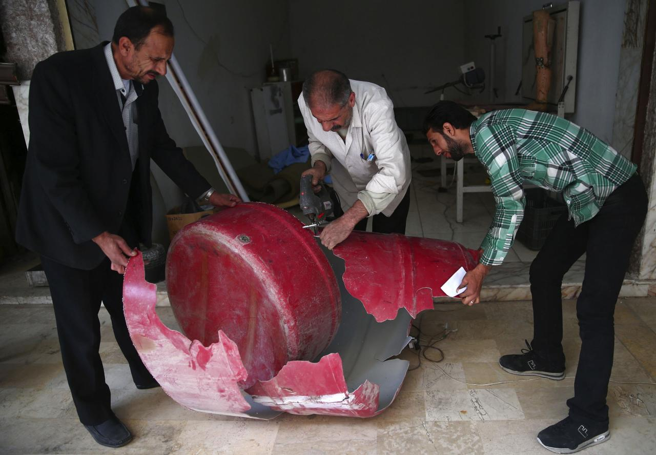 Workers use a water barrel to make prosthesis at a welfare workshop in the Duma neighbourhood in Damascus October 24, 2013. The centre produces prosthesis from different materials including remnants of weapons, plastic mannequins and water barrels, and offer them to physically disabled victims of the war. Picture taken October 24, 2013. REUTERS/Bassam Khabieh (SYRIA - Tags: SOCIETY CONFLICT)