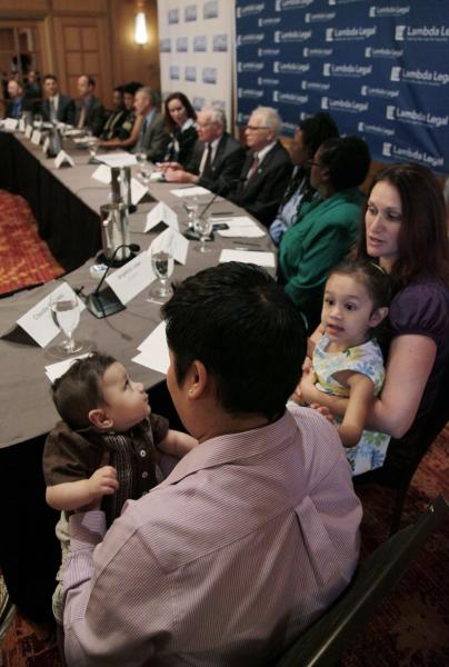 Claudia Mercado, left, holds her son Indigo Lopez-Mercado as Angelica Lopez right, holds the couples other child Isabel Lopez-Mercado as they gather for a news conference, Wednesday, May 30, 2012, in Chicago. More than two dozen gay Illinois couples who say it's unconstitutional for the state to deny them the right to marry and will file two lawsuits Wednesday, a move advocates believe could lead to legalized gay marriage in Illinois. The two lawsuits, filed by attorneys with the American Civil Liberties Union of Illinois and New-York based gay advocacy group Lambda Legal, include couples from Chicago and its suburbs, Bloomington and Marion. (AP Photo/M. Spencer Green)