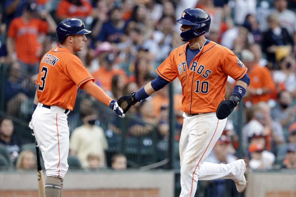 Houston Astros' Myles Straw (3) and Yuli Gurriel (10) celebrate after Gurriel scored on a single by Kyle Tucker during the second inning of a baseball game against the Texas Rangers on Friday, May 14, 2021, in Houston. (AP Photo/Michael Wyke)