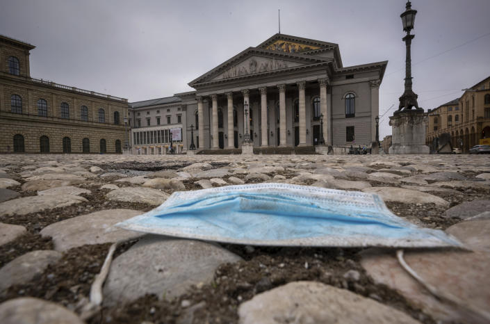 A blue mouth-nose protector lies on the pavement in front of the Bavarian State Opera in the centre of the city of Munich, Germany, during the lockdown on Tuesday, Jan. 5, 2020. (Peter Kneffel/dpa via AP)