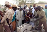Nigerian Minister of Finance laying the foundation for new classrooms at a school burned out by Boko Haram Islamist fighters in Chibok on March 5, 2015 (AFP Photo/Sunday Aghaeze)