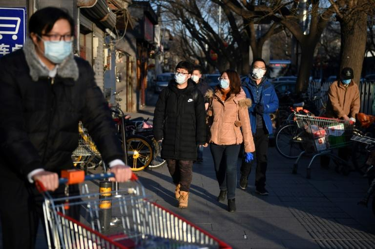 People wear masks to protect against the novel coronavirus  as they arrive at a market in Beijing on February 17, 2020