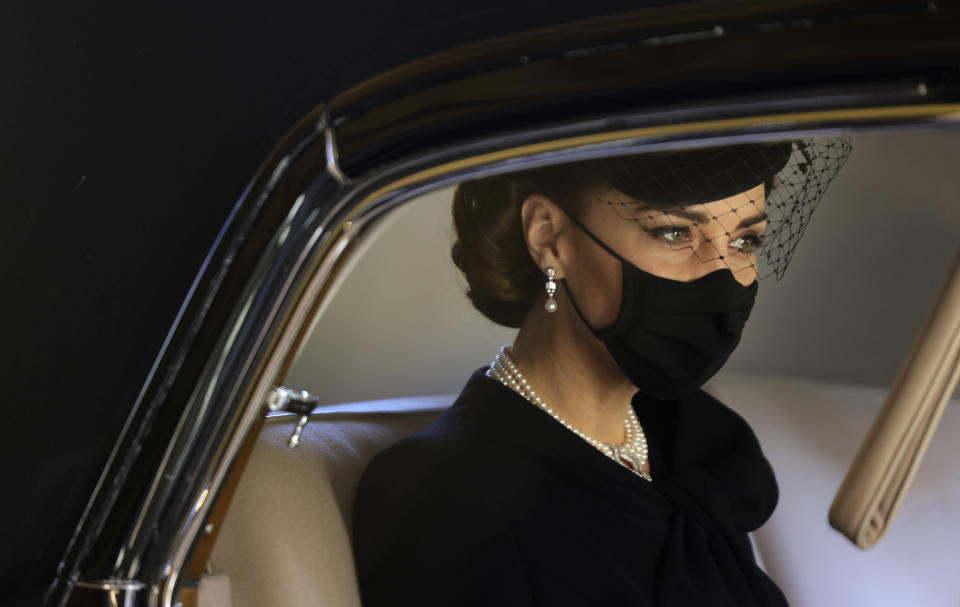 Kate, Duchess of Cambridge looks out from a car window as she arrives for the funeral of Britain's Prince Philip inside Windsor Castle in Windsor, England, Saturday, April 17, 2021. Prince Philip died April 9 at the age of 99 after 73 years of marriage to Britain's Queen Elizabeth II. (Chris Jackson/Pool via AP)