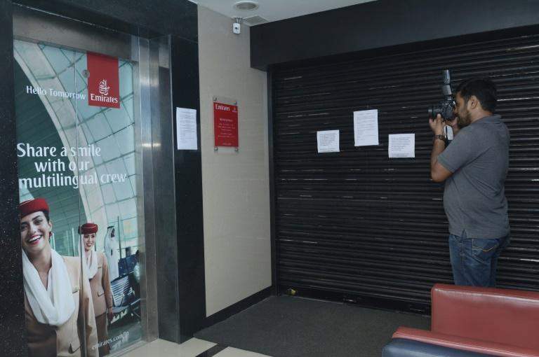 A photographer takes a picture of the closed Emirates airline office following an accident at Dubai International Airport on August 3, 2016