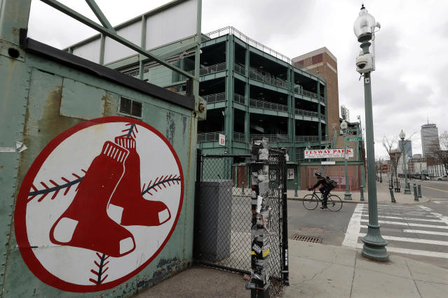 A cyclist rides past Fenway Park baseball park, March 25, 2020, in Boston. There will be empty ballparks on what was supposed to be Major League Baseball's opening day, with the start of the Major League Baseball regular season indefinitely on hold because of the coronavirus pandemic. (AP Photo/Steven Senne)