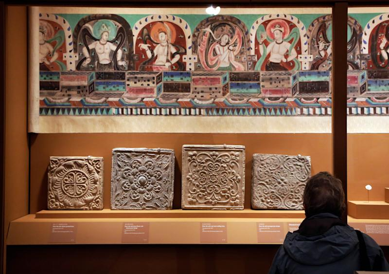 """Decorative floor tiles, and """"Celestial Music"""" from Mogao Cave 288, are displayed in """"Dunhuang: Buddhist Art at the Gateway of the Silk Road,"""" at the China Institute, in New York, Tuesday, April 24, 2013. (AP Photo/Richard Drew)"""