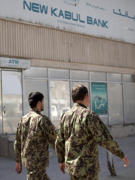 Afghan Army soldiers pass by a branch of the New Kabul Bank in the center of Kabul, Afghanistan, Tuesday, March 5, 2013. An Afghan tribunal convicted two top executives from Kabul Bank, renamed New Kabul Bank after the scandal broke, and sentenced them to five-year prison terms on Tuesday for their role in a massive corruption scandal that led to the collapse of Afghanistan's largest bank and threatened the country's fragile economy. The bank's former chairman Sherkhan Farnood and former chief executive officer Khalilullah Ferozi were guilty of theft of $278 million and $530 million, respectively. Farnood and Ferozi have also been ordered to pay back these funds. (AP Photo/Anja Niedringhaus)