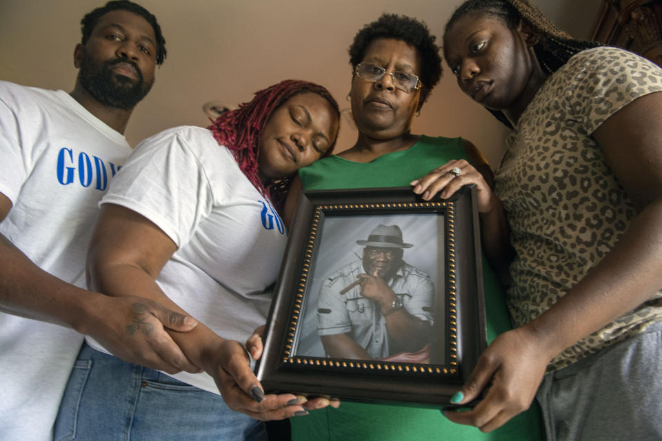 Janet Hartford, center, the wife of Anthony Hartford, 53, whose body was found among the dead on the Seacor Power, holds a photo of her husband while standing with her daughter, Antranae, 24, right, son, Thelonious Dukes, 38, far left, and daughter-in-law, Chantrice, at their home in New Orleans on Saturday, April 17, 2021. Divers returned Saturday to the murky, roiling waters of the Gulf of Mexico in search of lost crew members aboard a capsized lift boat off Louisiana, the Coast Guard said. (Chris Granger/The Times-Picayune/The New Orleans Advocate via AP)