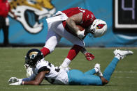Arizona Cardinals tight end Maxx Williams, right, hurdles Jacksonville Jaguars cornerback Tyson Campbell during the first half of an NFL football game, Sunday, Sept. 26, 2021, in Jacksonville, Fla. (AP Photo/Stephen B. Morton)