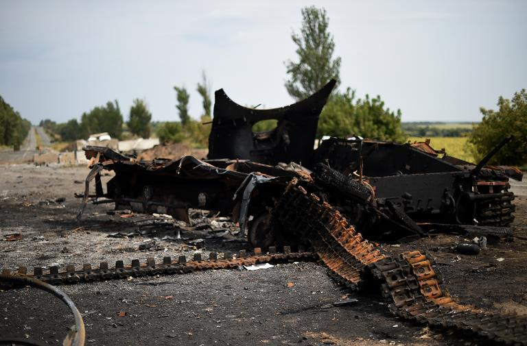 The wreckege of an aarmoured personnel carrier (APC) is seen at an abandoned checkpoint in Olenivka, Ukraine on September 1, 2014