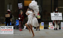 A dancer performs in protest opposite the Central Criminal Court, the Old Bailey, in London, Monday, Sept. 21, 2020, as the Julian Assange extradition hearing to the US continues. (AP Photo/Frank Augstein)