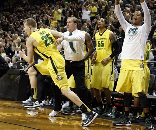 Oregon's E.J. Singler, left, runs downcourt past head coach Dana Altman and a celebrating Duck bench after sinking a three-point basket against Washington in an NCAA college basketball game in Eugene, Ore., Saturday, Jan 26, 2013. (AP Photo/Chris Pietsch)