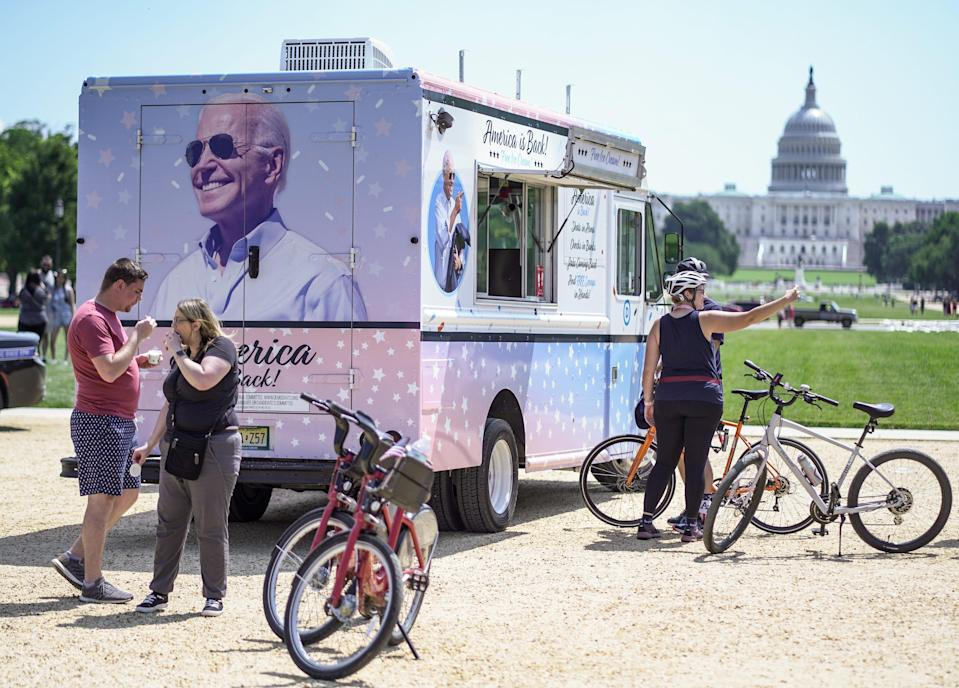 """People enjoy free ice cream at the """"America is Back"""" ice cream truck at the National Mall on July 4 in Washington."""