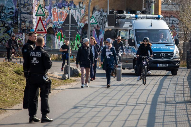 Patrolling police officers use a tannoy and screens mounted on a police van to address people gathering in Gleisdreieck park Berlin on March 28, 2020 amid the novel coronavirus pandemic. - Police patrolled parks and public spaces on Saturday as people was adviced to implement social distancing and not mingle in units more than two people at the time, but as the tempratue rose to high teens celsius in the German capital more people head out to greet the spring despite government advice to the opposite. (Photo by Odd ANDERSEN / AFP) (Photo by ODD ANDERSEN/AFP via Getty Images)