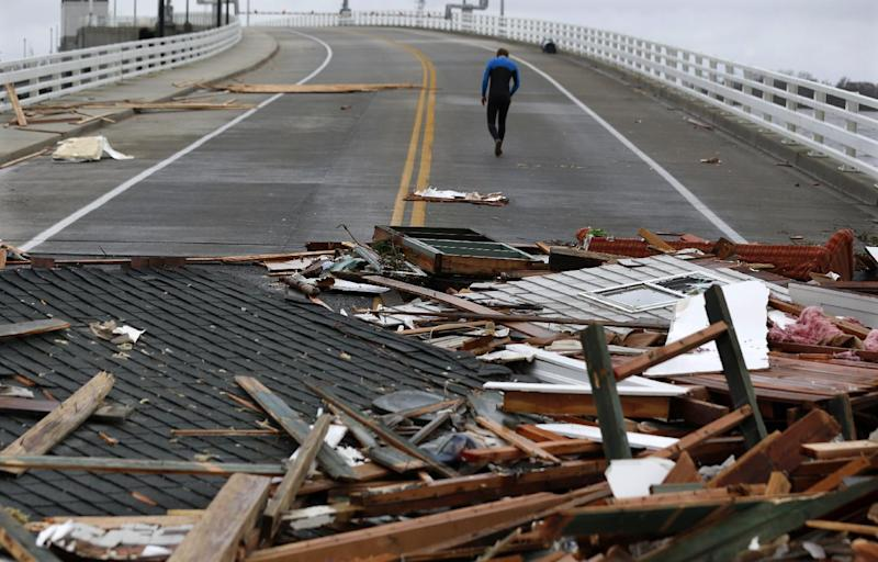 Currie Wagner walks away from the scene where the debris of his grandmother Betty Wagner's house ended up on top of the Mantoloking Bridge the morning after superstorm Sandy rolled through, Tuesday, Oct. 30, 2012, in Mantoloking, N.J. Sandy, the storm that made landfall Monday, caused multiple fatalities, halted mass transit and cut power to more than 6 million homes and businesses. (AP Photo/Julio Cortez)