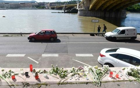 <span>Flowers and candles are left in memory of the victims at the Margaret Bridge, the spot of the accident involving South Korean tourists, in Budapest</span> <span>Credit: Noemi Bruzak/MTI </span>