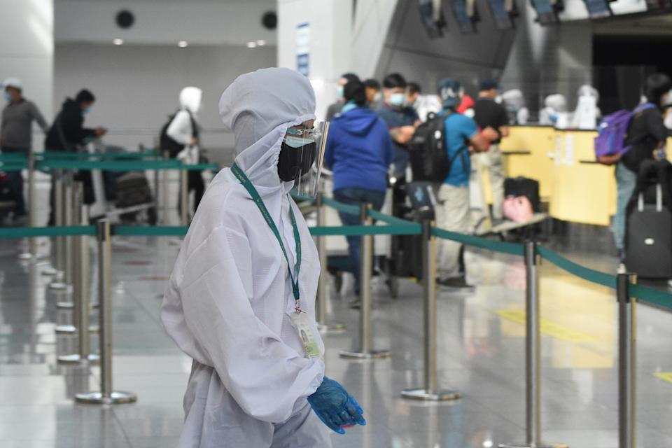 An international airline ground staff wearing protective gear works at the airport in Manila on August 4, 2020.