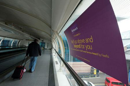 FILE PHOTO: A man walks past a Monarch airlines poster after the airline ceased trading, at Manchester airport in Britain, October 2, 2017. REUTERS/Andrew Yates