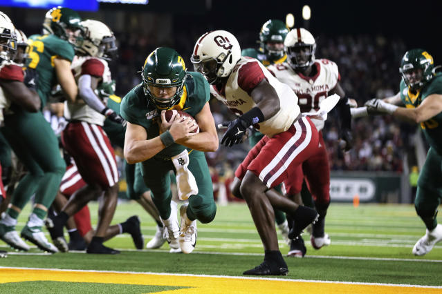 Baylor quarterback Charlie Brewer, left, dives into the end zone for a 4-yard touchdown as Oklahoma linebacker Kenneth Murray, right, defends during the first half of an NCAA college football game in Waco, Texas, Saturday, Nov. 16, 2019. (AP Photo/Ray Carlin)