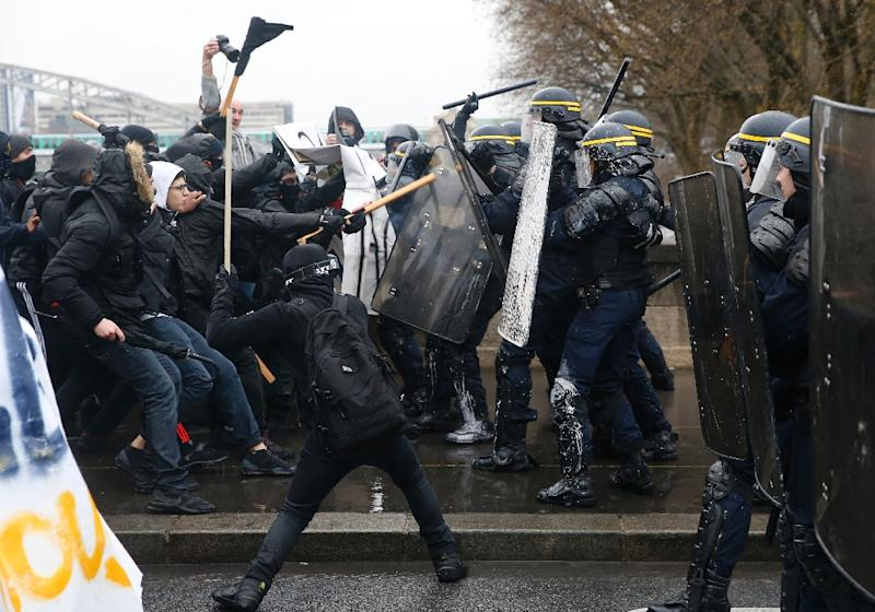 French riot police clash with union members and students demonstrating against labour law reforms  close to the Gare de Lyon train station in the French capital Paris on March 31, 2016