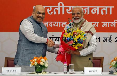 FILE PHOTO: India's Prime Minister Narendra Modi shakes hands with the Bharatiya Janata Party (BJP) President Amit Shah during a thanksgiving ceremony by BJP leaders to its allies at the party headquarters in New Delhi, India, May 21, 2019. REUTERS/Anushree Fadnavis/File Photo