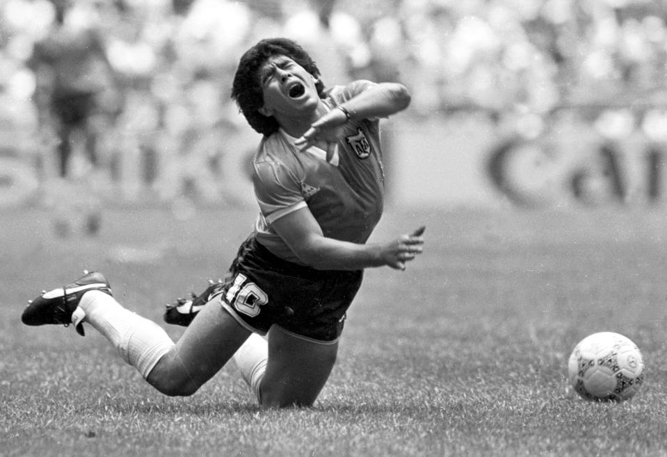 Argentina's Diego Maradona falls to the pitch after being tripped up in their World Cup quarterfinal match against England in Mexico City in this June 22, 1986 file photo. Maradona scored both goals in Argentina's 2-1 victory. Maradona remained in intensive care on Tuesday morning, more than 36 hours after falling ill with heart and breathing problems. A clutch of fans continued a vigil outside the posh Buenos Aires clinic where Maradona, one of the most gifted players in soccer history, was rushed on Sunday. Maradona arrived at the clinic in a serious, feverish condition with breathing difficulties and a swollen heart after watching a game at his former club Boca Juniors' stadium where he made his name. (B/W ONLY) REUTERS/Gary Hershorn  GMH