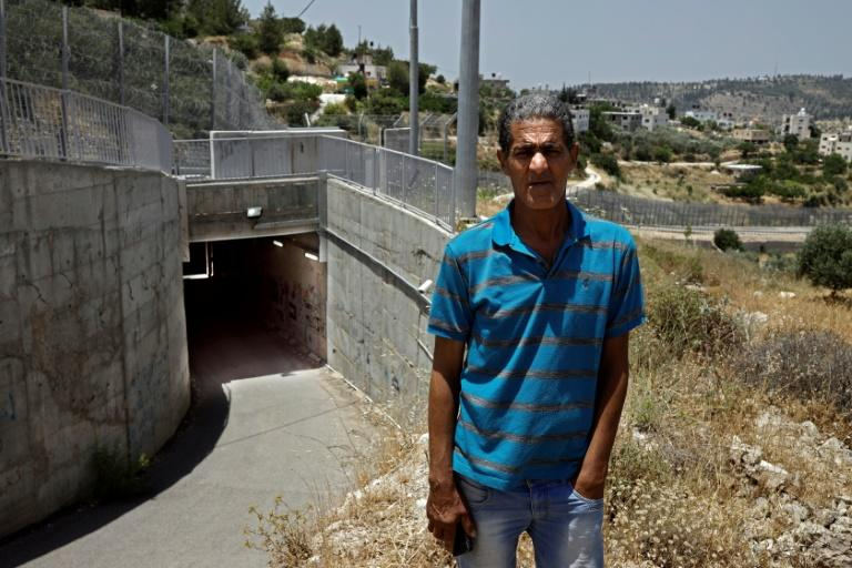 Palestinian Omar Hajajla stands in front of the tunnel that connects Jerusalem to his village in the occupied West Bank (AFP Photo/THOMAS COEX)