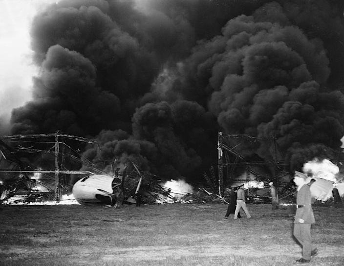 <p>Black smoke rises from the skeleton of the burning Hindenburg airship at Lakehurst, N.J., May 6, 1937. The German-built zeppelin caught fire and exploded mid-air as it was landing after its transatlantic voyage, carrying 97 passengers and crew. Thirty-five people on board and one ground crew member were killed. (AP Photo/Murray Becker) </p>