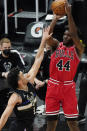 Chicago Bulls forward Patrick Williams, right, shoots over Milwaukee Bucks guard Elijah Bryant during the first half of an NBA basketball game in Chicago, Sunday, May 16, 2021. (AP Photo/Nam Y. Huh)