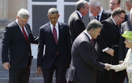 Canada's Prime Minister Stephen Harper (L) and U.S. President Barack Obama (2nd L) take their spots as Ukraine's President-elect Petro Poroshenko shakes hands with Britain's Queen Elizabeth during a family photo for the 70th anniversary of the D-Day landings in Benouville June 6, 2014. REUTERS/Kevin Lamarque
