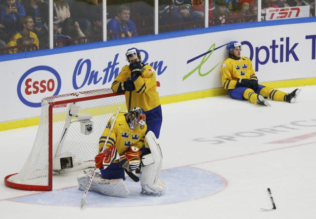 Sweden's goalie Oscar Dansk, Robert Hagg (C), and Elias Lindholm (R) react to losing to Finland in overtime of their IIHF World Junior Championship gold medal ice hockey game in Malmo, Sweden, January 5, 2014. REUTERS/Alexander Demianchuk (SWEDEN - Tags: SPORT ICE HOCKEY)