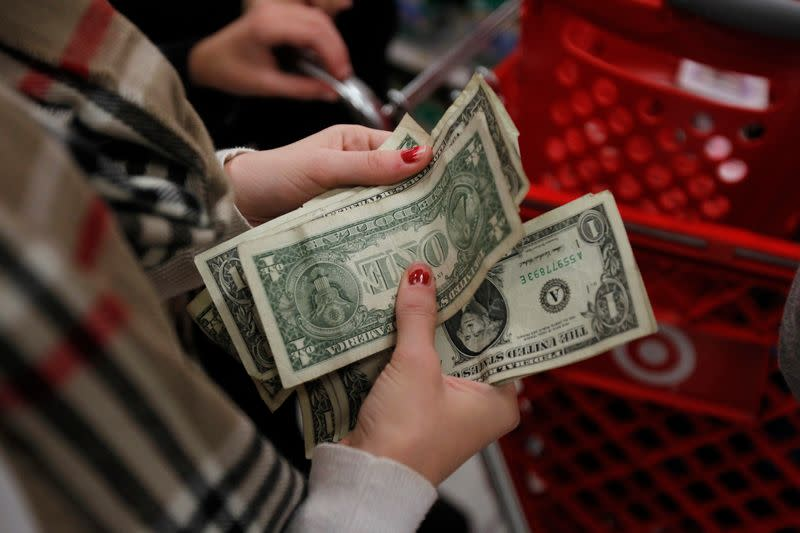 """A customer counts her money while waiting in line to check out at a Target store on the shopping day dubbed """"Black Friday"""" in Torrington"""