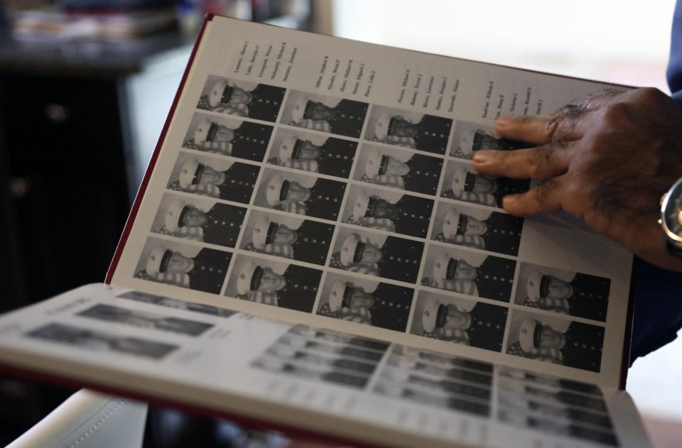 Mansoor Shams looks through photos from his time in the Marines, Friday Aug. 13, 2021 at his home in Baltimore. (AP Photo/Jessie Wardarski)