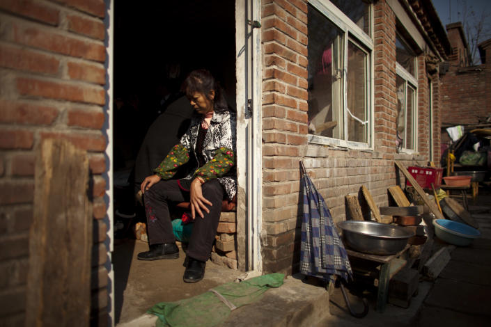 """A newly-arrived petitioner from southern China's Hunan province rests on a bed of a rental room that was raided by unidentified men a week ago, on the outskirts of Beijing Tuesday, Nov. 6, 2012. The woman has been petitioning to draw central government attention to get back her compensation from local government after a forced home relocation. """"There is no law in China, especially for us petitioners and ordinary folk,"""" another petitioner said in an interview with The Associated Press, complaining about the impunity with which authorities detain """"petitioners"""" - people who bring local complaints directly to the central government in an age-old Chinese tradition that has continued during the Communist Party era. (AP Photo/Alexander F. Yuan)"""