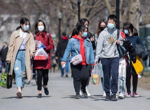People wear face masks as they walk in a park in Quebec.