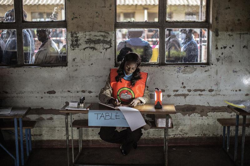 An electoral agent checks a voters roll as Zambians queue to cast their ballots in the presidential elections at Kanyama primary in Lusaka on January 20, 2015 (AFP Photo/Gianluigi Guercia)